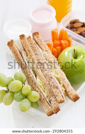school lunch with sandwich on white wooden table, vertical, close-up - stock photo