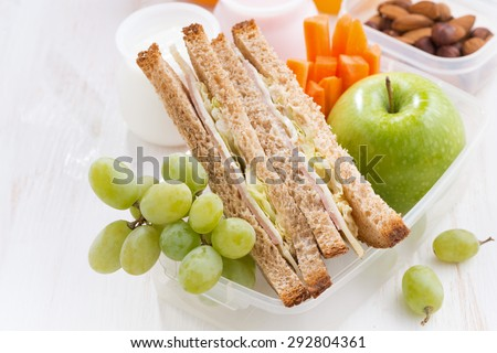 school lunch with sandwiches and fruit, top view, close-up, horizontal - stock photo