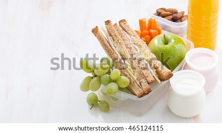 school lunch with sandwiches, fruit and yogurt on white background, horizontal