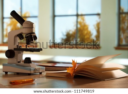 School microscope in classroom on window background - stock photo
