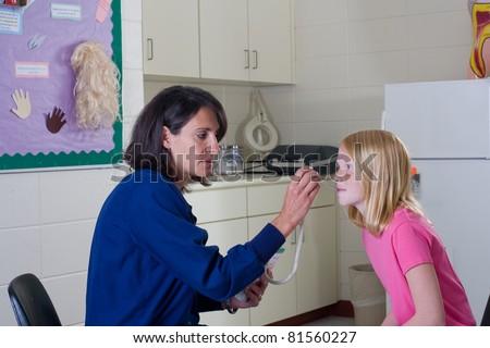 School nurse checking temperature of student patient. - stock photo