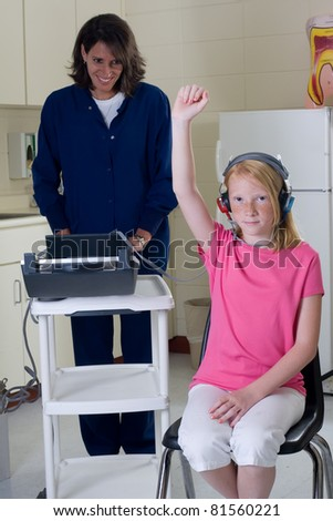 School nurse giving hearing test to student patient. - stock photo