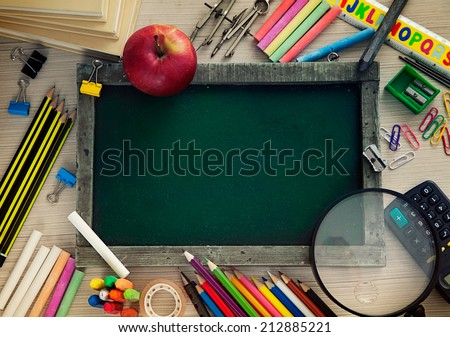 School objects for students. Chalkboard, pencils, crayons and apple - stock photo