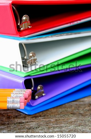 School or business supplies.  4 binders and pencils, used a shallow DOF with focus on the erasers. - stock photo