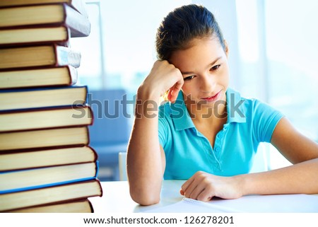 School pupil being frustrated with the amount of books to read - stock photo