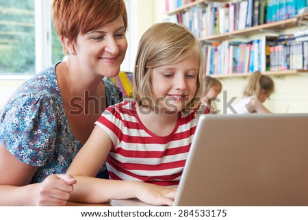 School Pupil With Teacher Using Laptop Computer In Classroom - stock photo
