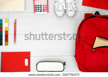 School set with backpack, shoes and supplies on light wooden background - stock photo