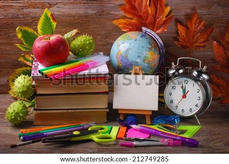 school stuffs with small easel,autumn chestnuts  and alarm clock on wooden background - stock photo
