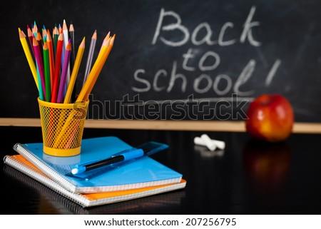 School supplies against blackboard. - stock photo
