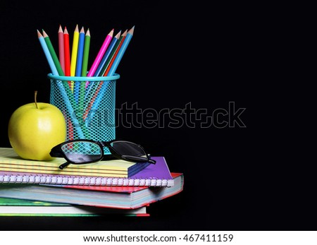 School Supplies. An apple, colored pencils and glasses on pile of books.