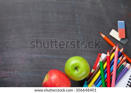 School supplies and apples on blackboard background. Top view with copy space - stock photo