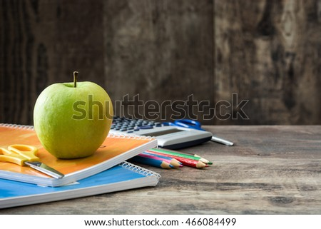 School supplies and green apple on rustic wooden background