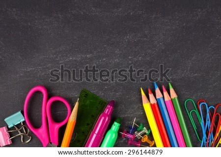 School supplies bottom border on a chalkboard background - stock photo
