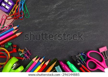 School supplies bottom corner border on a chalkboard background - stock photo