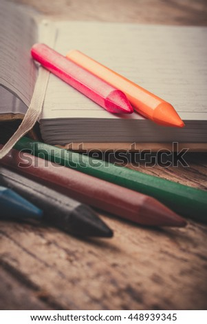 School supplies lying on a wooden table.