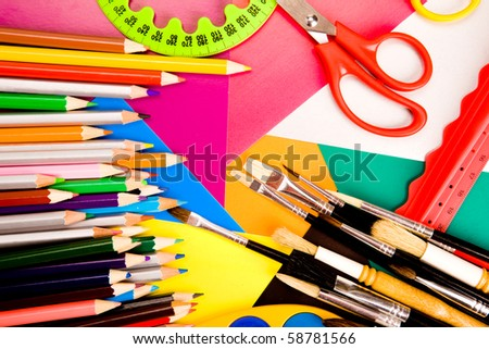 School supplies lying on colorful cardboard sheets