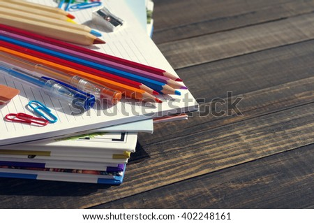 School supplies on a wooden old surface. Books, notebooks, handles, colored pencils on a wooden table - stock photo