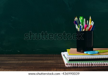 School supplies on a wooden surface against a blackboard. Books, notebooks, handles, colored pencils and rulers in a glass on a wooden table - stock photo