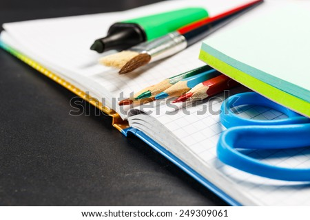 School supplies on black background - stock photo
