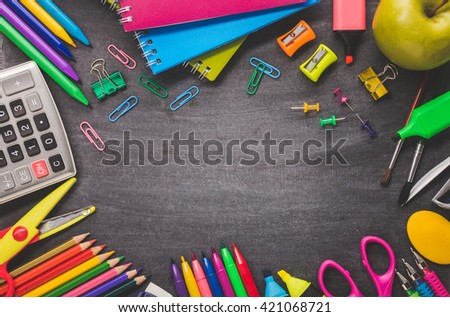School supplies on blackboard background. back to school concept - stock photo