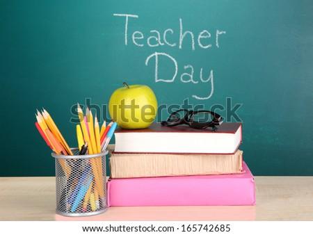 School supplies on blackboard background with inscription Teacher Day - stock photo