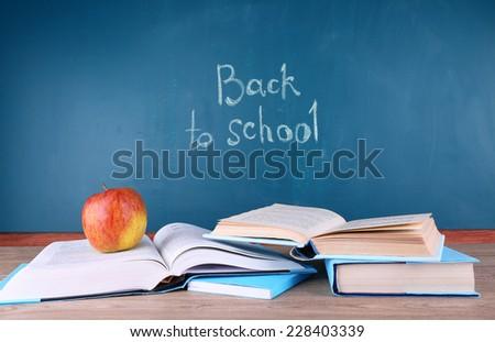 School supplies on table on blackboard background - stock photo