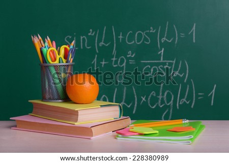 School supplies on table on board background - stock photo