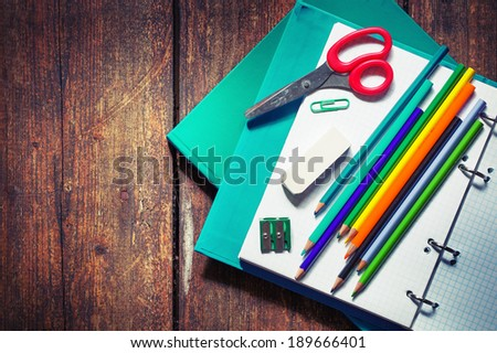 School supplies on wooden background - stock photo
