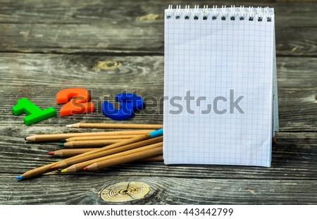 school supplies on wooden background, Notepad, pencils and numbers - stock photo