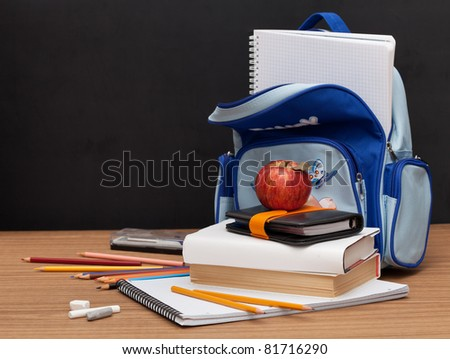 School Supplies with apple on black desk background - stock photo