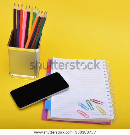 School supplies with smartphone on notepad - stock photo