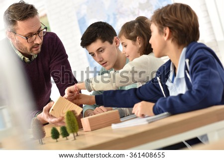 School teacher in science class with pupils  - stock photo