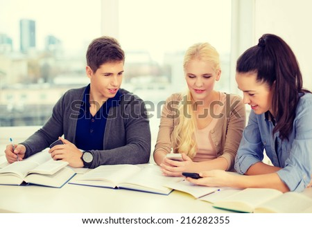 school, technology, internet and education concept - group of smiling students with smartphones and notebooks at school - stock photo