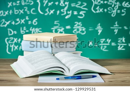 School textbooks on a desk in front of blackboard - stock photo