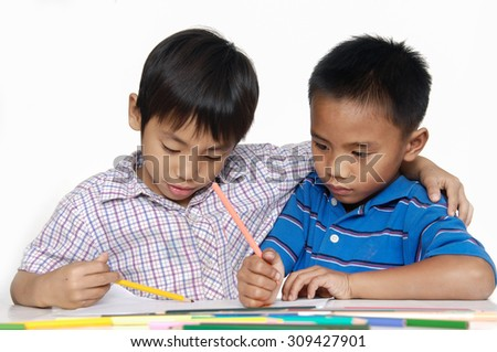 School two little boy sitting and writing in books - stock photo