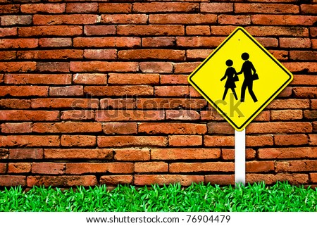 school warning traffic symbol sign on brick wall background and grass field