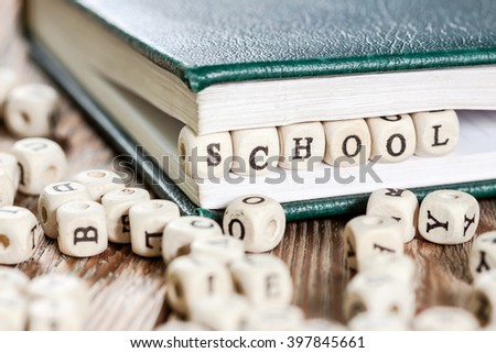 School word written on a wooden block in a book. On old wooden table.