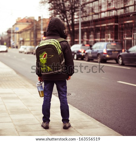 schoolboy alone in the street  - stock photo