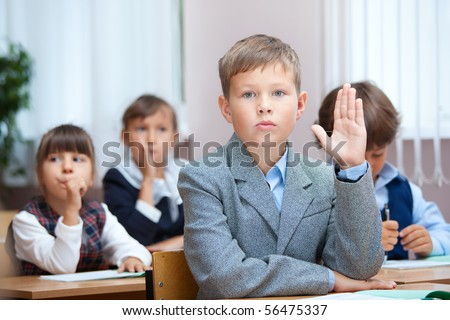 Schoolboy answer on question. Real lesson in classroom - stock photo