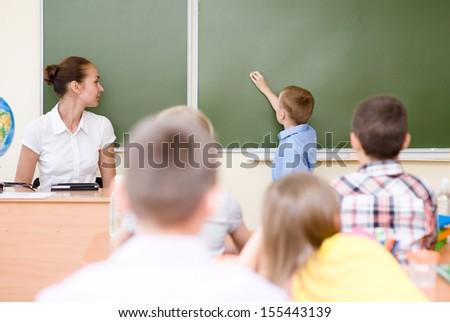 schoolboy answers questions of teachers near a school board - stock photo