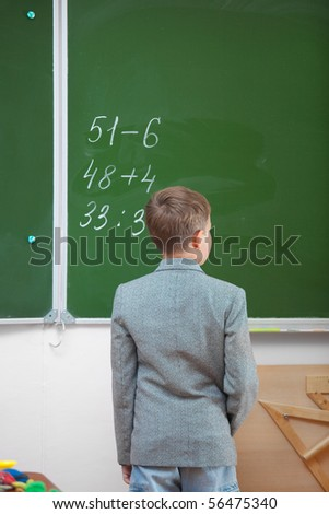 Schoolboy at the blackboard. Real lesson in classroom - stock photo