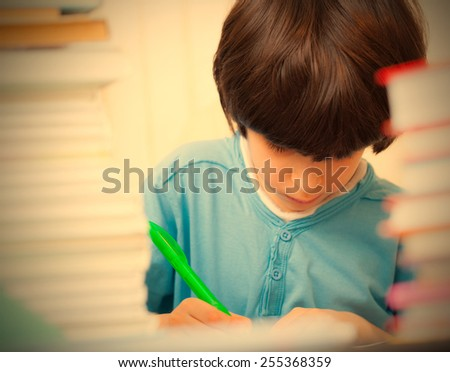 schoolboy doing homework in the library. copy space. instagram image retro style - stock photo