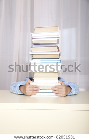 schoolboy hiding behind a big stack of thick books. - stock photo