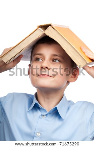 Schoolboy holding a big book on his head - stock photo