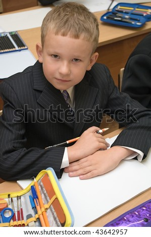 Schoolboy in suit sitting on the lecture at desk and looking on camera