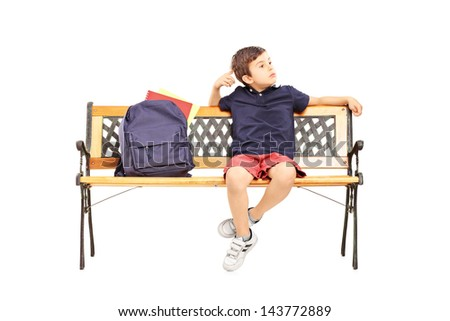 Schoolboy in thoughts sitting on a wooden chair isolated on white background - stock photo