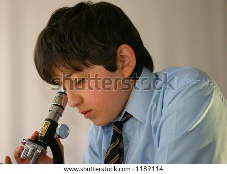 Schoolboy in uniform studies a specimen under the microscope - stock photo