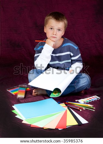 schoolboy is sitting on floor and thinking - studio photo - stock photo