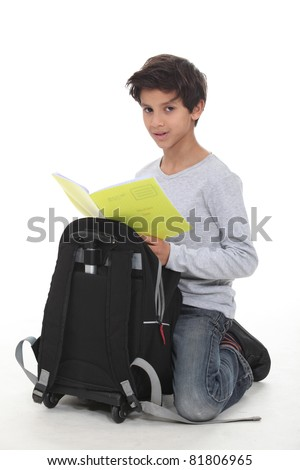 Schoolboy kneeling by backpack - stock photo