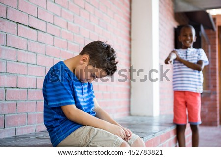 Schoolboy laughing on sad classmate in corridor at school - stock photo